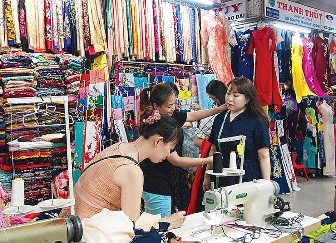 May áo dài lấy ngày ở chợ Hàn là trải nghiệm độc đáo trong chuyến du lịch Đà Nẵng. Ảnh: congthuong.vn
